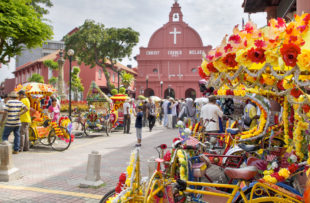 MELAKA, MALAYSIA - JAN 14 : Christ Church Melaka on Jan 14, 2012 in Melaka Malaysia. A popular historic tourist attraction in Melaka Malaysia with flower decorated tricycles for hire.